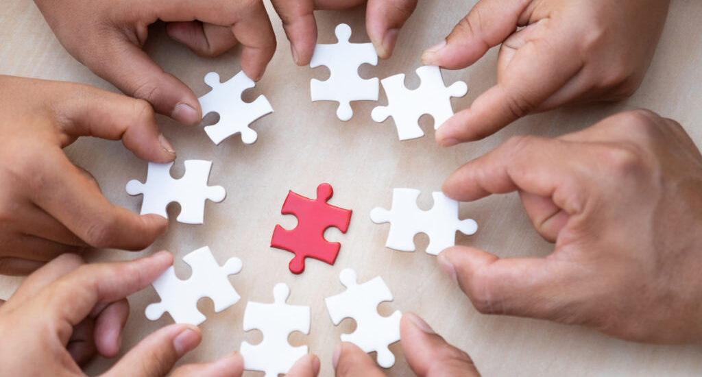 Hands holding piece of blank jigsaw puzzle with wooden table background.