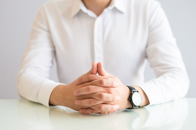 Closeup of man sitting at table with his hands clasped. Male person wearing shirt and watch. Concentration or waiting concept. Cropped front view.